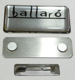 Crachá de aço inox com logotipo da empresa e espaço para fixação do nome do colaborador. Fixação por imã ou alfinete.
