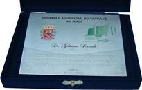 Placa de homenagem entregue ao prefeito de São Paulo no aniversário de 40 anos de um hospital pelo trabalho e empenho dedicado à área de saúde.