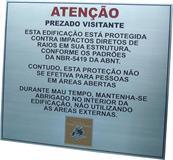 Placa de sinalização com aviso ao visitante de edificação protegida contra impacto de raios.
