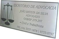Placa de sinalização de escritório com símbolo da advocacia e dados do advogado.