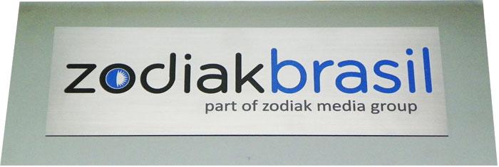 Placa de sinalização de porta de empresa com logotipo e placa sobreposta.