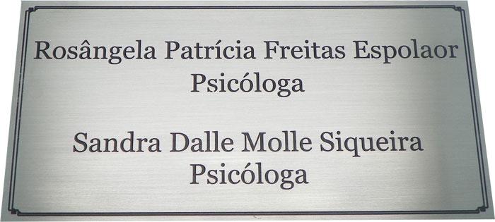 Placa de sinalização de porta de consultório médico indicando nomes e profissões das Drªs