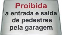 Placa de sinalização com aviso de proibida a entrada e saída de pedestres pela garagem.